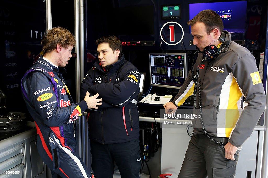 Sebastian Vettel of Germany and Infiniti Red Bull Racing speaks with Tim Malyon (C) the Infiniti Red Bull Racing Performance Engineer in the team garage during Formula One winter testing at Circuito de Jerez on February 8, 2013 in Jerez de la Frontera, Spain.