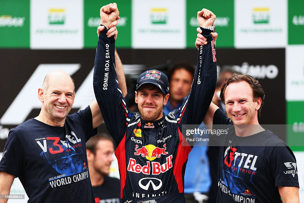 Sebastian Vettel (C) of Germany and Red Bull Racing celebrates with Red Bull Racing Chief Technical Officer Adrian Newey (L) and Team Principal Christian Horner (R) on the podium as he finishes in sixth position and clinches his third consecutive drivers world championship during the Brazilian Formula One Grand Prix at the Autodromo Jose Carlos Pace on November 25, 2012 in Sao Paulo, Brazil.