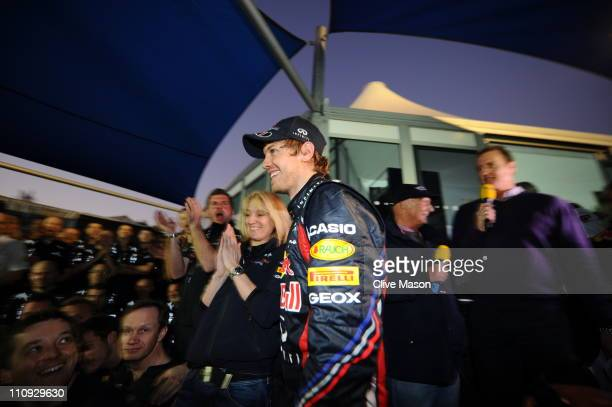 Sebastian Vettel of Germany and Red Bull Racing celebrates with team mates in the paddock after winning the Australian Formula One Grand Prix at the...