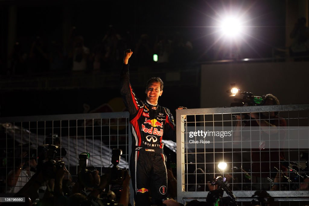 Sebastian Vettel of Germany and Red Bull Racing celebrates with team mates in the pitlane after finishing third to secure his second F1 World Drivers Championship during the Japanese Formula One Grand Prix at Suzuka Circuit on October 9, 2011 in Suzuka, Japan.