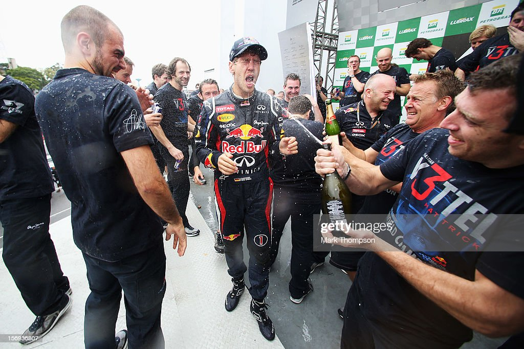 Sebastian Vettel of Germany and Red Bull Racing celebrates with team mates on the podium as he finishes in sixth position and clinches the drivers world championship during the Brazilian Formula One Grand Prix at the Autodromo Jose Carlos Pace on November 25, 2012 in Sao Paulo, Brazil.