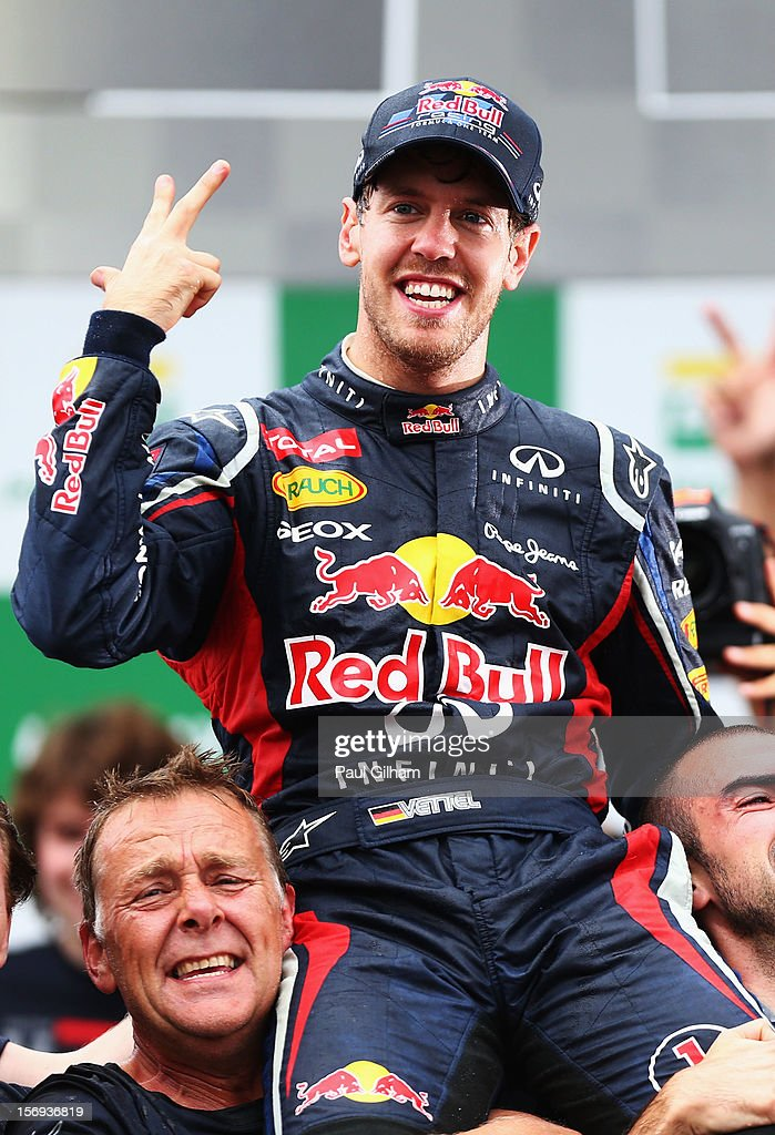 Sebastian Vettel of Germany and Red Bull Racing celebrates with team mates on the podium as he finishes in sixth position and clinches his third consecutive drivers world championship during the Brazilian Formula One Grand Prix at the Autodromo Jose Carlos Pace on November 25, 2012 in Sao Paulo, Brazil.