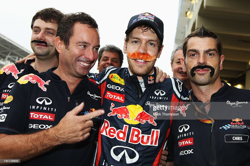 Sebastian Vettel (C) of Germany and Red Bull Racing is seen wearing a false moustache as he celebrates breaking Nigel Mansells record after securing pole position for the fifteenth time this season following qualifying for the Brazilian Formula One Grand Prix at the Autodromo Jose Carlos Pace on November 26, 2011 in Sao Paulo, Brazil.