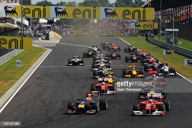 Sebastian Vettel of Germany and Red Bull Racing leads Fernando Alonso of Spain and Ferrari into the first corner at the start of the the Hungarian...