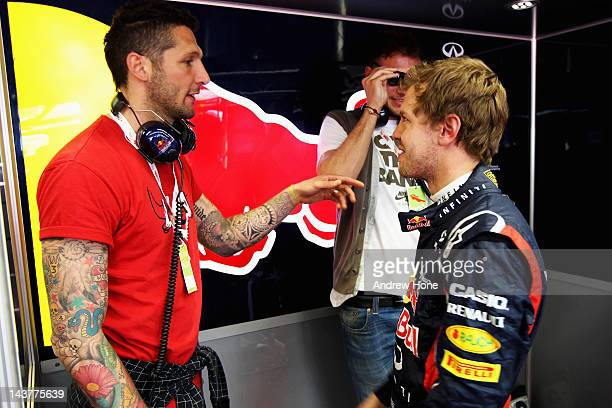 Sebastian Vettel of Germany and Red Bull Racing meets Italian footballer Marco Materazzi in his Red Bull team garage during Formula One Testing at...