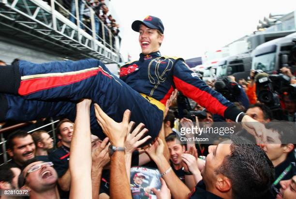 Sebastian Vettel of Germany and Scuderia Toro Rosso is thrown high in the air by team mates in the paddock after winning the Italian Formula One...