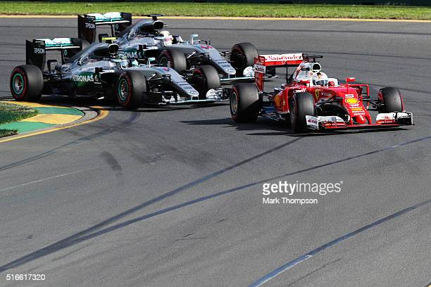 Sebastian Vettel of Germany drives the Scuderia Ferrari SF16H Ferrari 059/5 turbo ahead of Nico Rosberg of Germany drives the Mercedes AMG Petronas...