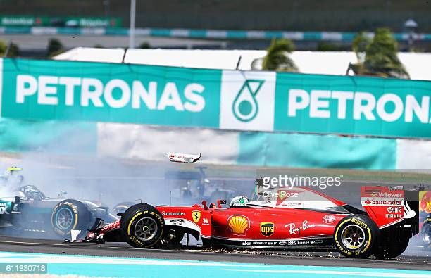 Sebastian Vettel of Germany driving the Scuderia Ferrari SF16H Ferrari 059/5 turbo with a broken front suspension as Nico Rosberg of Germany driving...