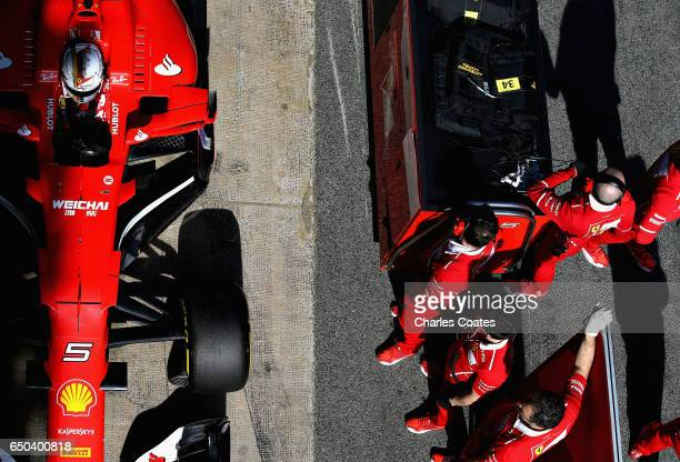 Sebastian Vettel of Germany driving the Scuderia Ferrari SF70H and the Ferrari team prepare for a race simulation in the Pitlane during day three of...