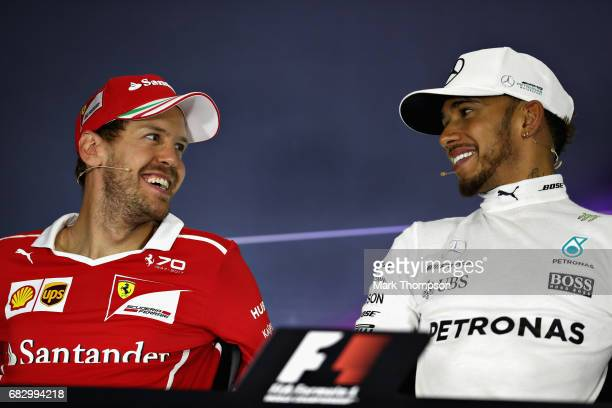 Sebastian Vettel of Germany driving the Scuderia Ferrari SF70H and Lewis Hamilton of Great Britain and Mercedes GP talk in the post race press...
