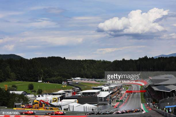 Sebastian Vettel of Germany driving the Scuderia Ferrari SF70H and Kimi Raikkonen of Finland driving the Scuderia Ferrari SF70H round turn one at the...