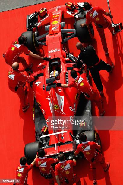 Sebastian Vettel of Germany driving the Scuderia Ferrari SF70H is pushed by his mechanics in the Pitlane during qualifying for the Formula One Grand...