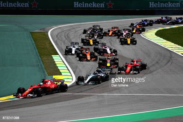 Sebastian Vettel of Germany driving the Scuderia Ferrari SF70H leads Valtteri Bottas driving the Mercedes AMG Petronas F1 Team Mercedes F1 WO8 into...
