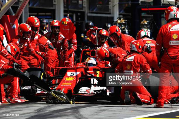 Sebastian Vettel of Germany driving the Scuderia Ferrari SF70H makes a pit stop for new tyres during the Formula One Grand Prix of Hungary at...