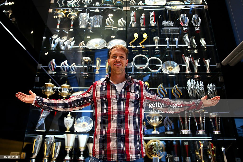 Sebastian Vettel of Germany poses next to the Infiniti red Bull Racing trophy cabinet during a visit to the Red Bull Racing Factory on December 2, 2014 in Milton Keynes, England.