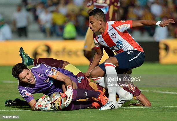 Sebastian Viera goalkeeper of Junior catches the ball in front of Johnatan Estrada and William Tesillo during a first leg match between Deportes...