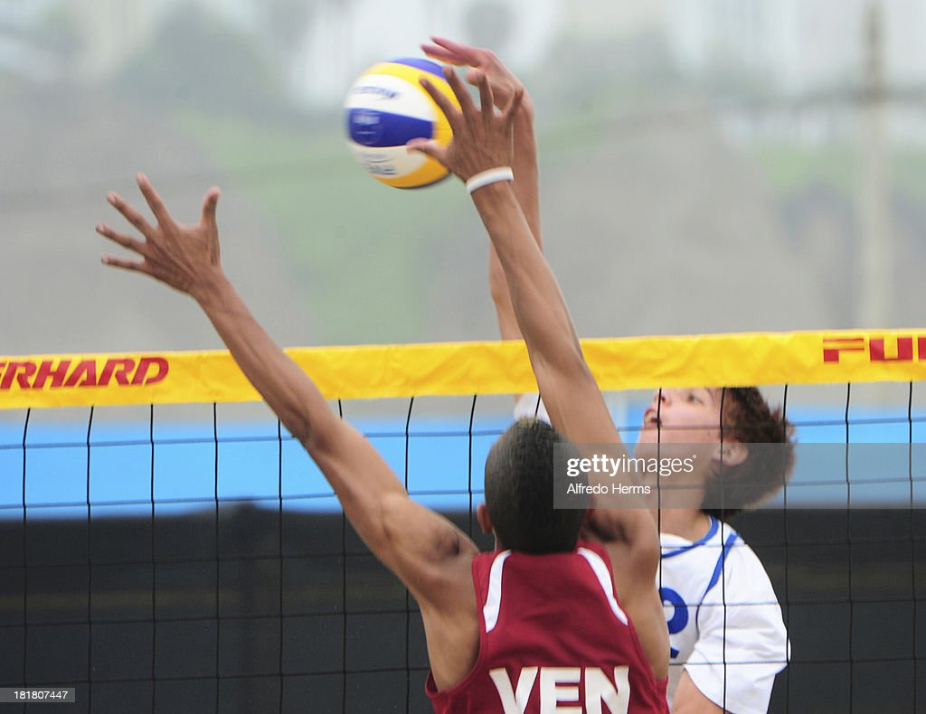 Sebastian Vieyto Acosta of Uruguay spikes as Ronaldo Martinez of Venezuela blocks during the Men's Beach Volleyball Semi Final as part of the I ODESUR South American Youth Games at Parque Tematico de los Deportes on September 25, 2013 in Lima, Peru.