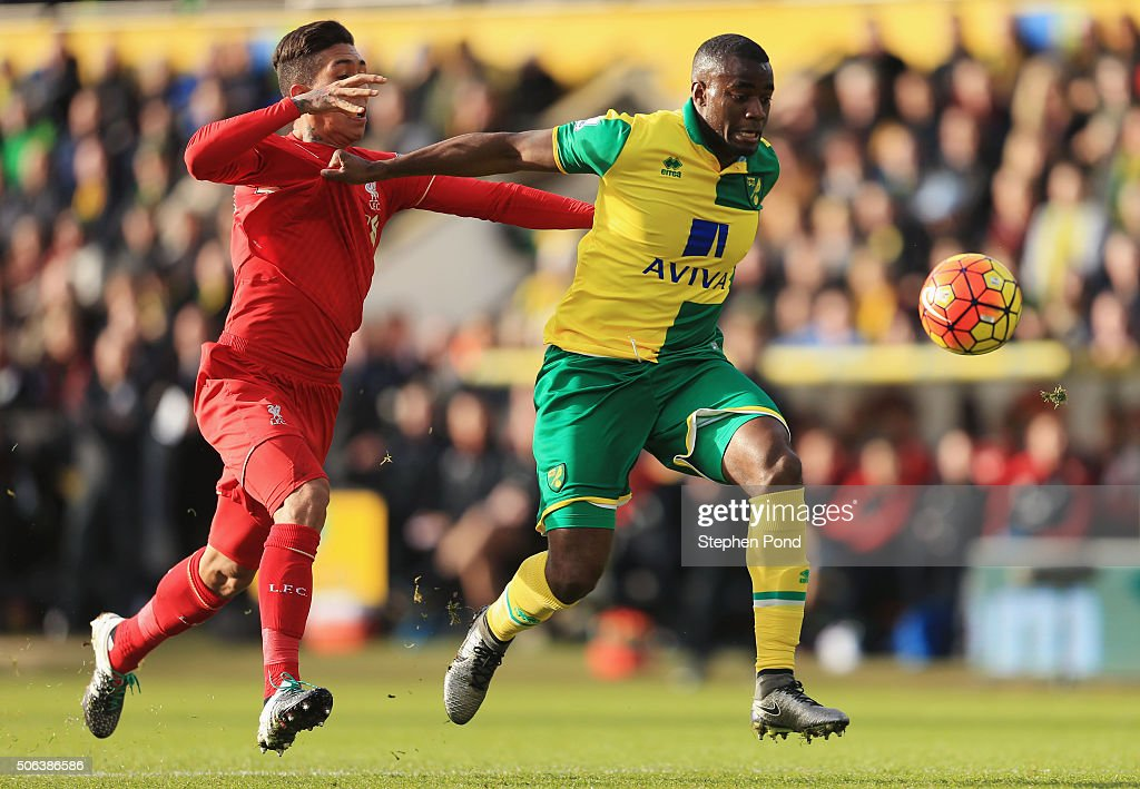 Sebastien Bassong of Norwich City and Roberto Firmino of Liverpool compete for the ball during the Barclays Premier League match between Norwich City...