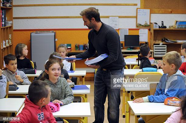 Sebastien Galivelle director of the elementary school 'Les Eterlous' dispenses notebooks to his pupils in his classroom on August 26 2014 in...