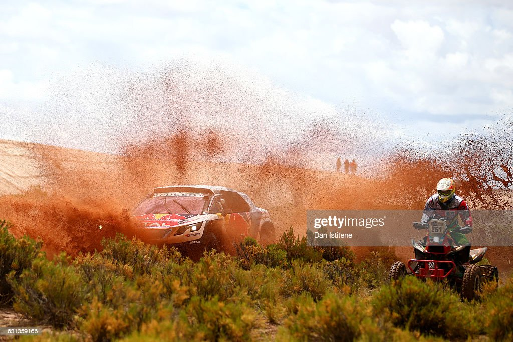 Sebastien Loeb of France and Peugeot Total drives with co-driver Daniel Elena of Monaco in the 3008 DKR Peugeot car in the Classe : T1.4 2 Roues Motrices, Diesel next to Santiago Hansen of Argentina and Honda MEC rides a TRX700XX Honda quad bike in the Classe : 4 x 2 0 a 750 cm3 during stage seven of the 2017 Dakar Rally between La Paz and Uyuni on January 9, 2017 at an unspecified location in Bolivia.