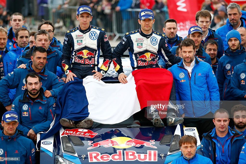 Sebastien Ogier and <a gi-track='captionPersonalityLinkClicked' href=/galleries/search?phrase=Julien+Ingrassia&family=editorial&specificpeople=4947850 ng-click='$event.stopPropagation()'>Julien Ingrassia</a> of France and Volkswagen Motorsport team members pose with the French tricolor as a mark of respect for the victims of the tragic events of the FIA World Rally Championship Great Britain on November 15, 2015 in Deeside, Wales.