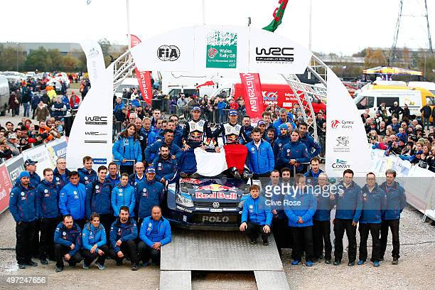 Sebastien Ogier and Julien Ingrassia of France and Volkswagen Motorsport team members pose with the French tricolor as a mark of respect for the...