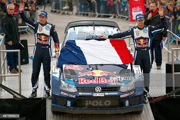 Sebastien Ogier and Julien Ingrassia of France and Volkswagen Motorsport team place the French tricolor on their winning car as a mark of respect for...