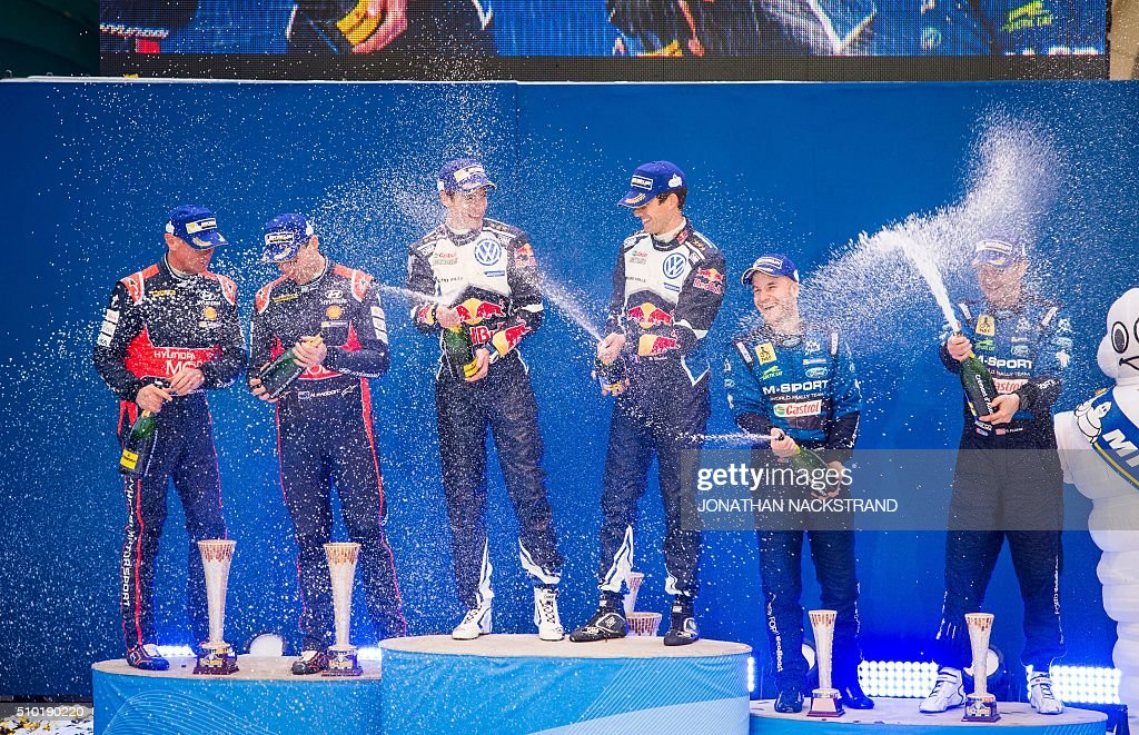 Sebastien Ogier of France and his co-driver Julien Ingrassia (C) celebrate with second placed Hayden Paddon of New Zeeland and his co-driver John Kennard (L) and Mads Ostberg of Norway and his co-driver Ola Floene during the winner's ceremony of Rally Sweden, second round of the FIA World Rally Championship on February 14, 2016 in Karlstad, Sweden. / AFP / JONATHAN NACKSTRAND