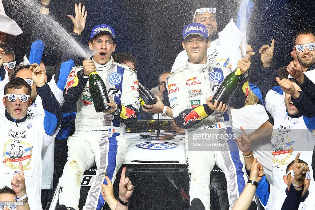 Sebastien Ogier of France and <a gi-track='captionPersonalityLinkClicked' href=/galleries/search?phrase=Julien+Ingrassia&family=editorial&specificpeople=4947850 ng-click='$event.stopPropagation()'>Julien Ingrassia</a> of France celebrate their World Rally Title with all the Volkswagen Motorsport staff members on the final podium in Strasbourg on Day Three of the WRC France on October 6, 2013 in Strasbourg, France.