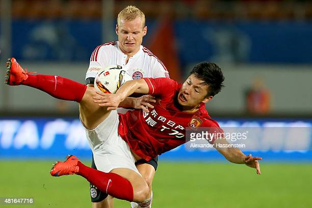 Sebastin Rode of Muenchen battles for the ball with Long Zheng of Guangzhou during the international friendly match between FC Guangzhou Evergrande...