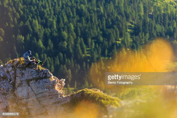 15/07/2017 Secede, Dolomite, Italy : Small man sitting on the top of the rock in Seceda