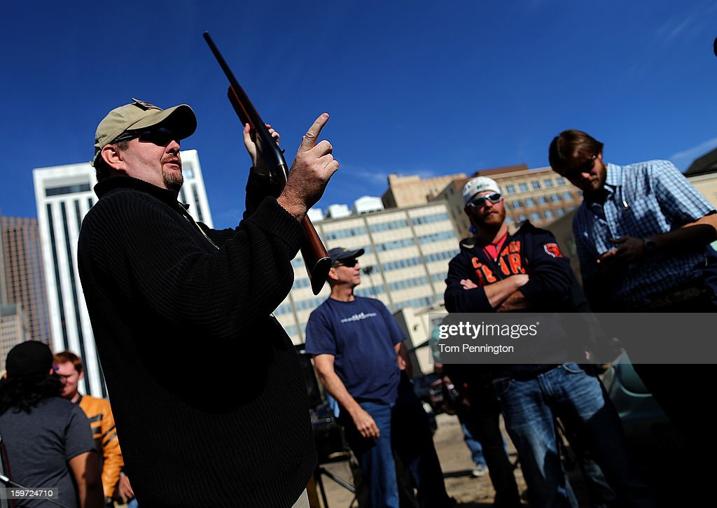 Second Amendment supporter and gun enthusiast Derek Ringley displays an unloaded shotgun that was being sold in an impromptu auction across the street from a gun buy back program at the First Presbyterian Church of Dallas on January 19, 2013 in Dallas, Texas. U.S. President Barack Obama recently unveiled a package of gun control proposals that include universal background checks and bans on assault weapons and high-capacity magazines.