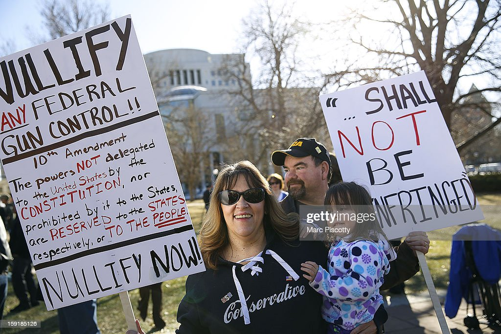 Second Amendment supporter Debora Yates holds her three year-old daughter Reagan as she protests with her husband Glen Yates in support for gun ownership on January 9, 2013 at the Colorado State Capitol in Denver, Colorado. The Yates are NRA members and live in Bailey, Colorado. Lawmakers are calling for tougher gun legislation after recent mass shootings at an Aurora, Colorado movie theater and at Sandy Hook Elementary School in Newtown, Connecticut.