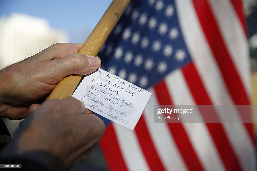 A Second Amendment supporter shows off a section of the U.S. Flag Code on January 9, 2013 at the Colorado State Capitol in Denver, Colorado. Lawmakers are calling for tougher gun legislation after recent mass shootings at an Aurora, Colorado movie theater and at Sandy Hook Elementary School in Newtown, Connecticut.