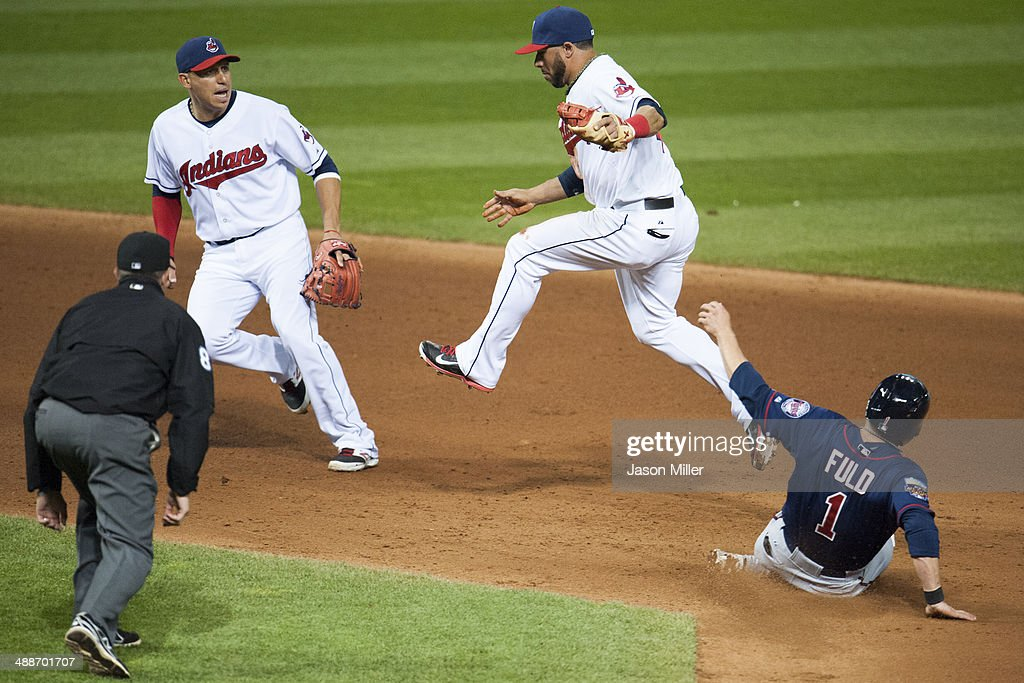 Second base umpire Cory Blaser #89 watches as shortstop <a gi-track='captionPersonalityLinkClicked' href=/galleries/search?phrase=Asdrubal+Cabrera&family=editorial&specificpeople=834042 ng-click='$event.stopPropagation()'>Asdrubal Cabrera</a> #13 backs up second baseman <a gi-track='captionPersonalityLinkClicked' href=/galleries/search?phrase=Mike+Aviles&family=editorial&specificpeople=4944765 ng-click='$event.stopPropagation()'>Mike Aviles</a> #4 of the Cleveland Indians forces out <a gi-track='captionPersonalityLinkClicked' href=/galleries/search?phrase=Sam+Fuld&family=editorial&specificpeople=4505687 ng-click='$event.stopPropagation()'>Sam Fuld</a> #1 of the Minnesota Twins at second during the seventh inning at Progressive Field on May 7, 2014 in Cleveland, Ohio. The Indians defeated the Twins 4-3.