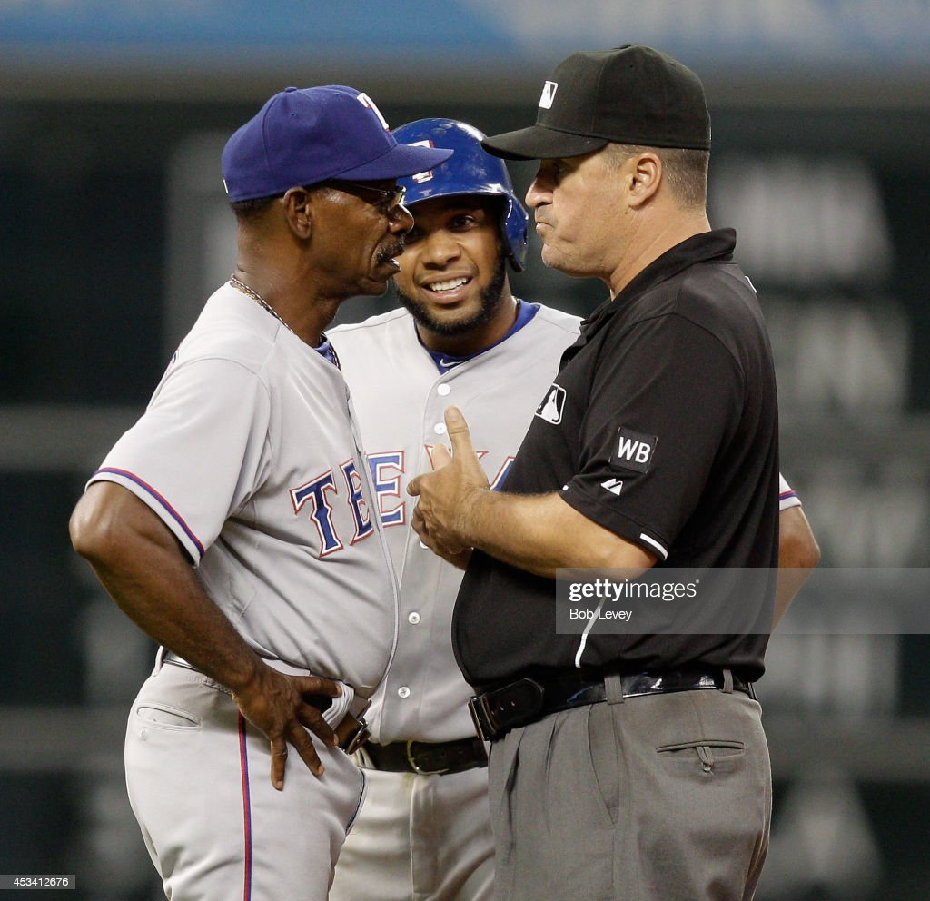 Second base umpire David Rackley explains to <a gi-track='captionPersonalityLinkClicked' href=/galleries/search?phrase=Ron+Washington&family=editorial&specificpeople=225012 ng-click='$event.stopPropagation()'>Ron Washington</a> #38 of the Texas Rangers why <a gi-track='captionPersonalityLinkClicked' href=/galleries/search?phrase=Elvis+Andrus&family=editorial&specificpeople=4845974 ng-click='$event.stopPropagation()'>Elvis Andrus</a> #1 was called out at second base in the sixth inning against the Houston Astros at Minute Maid Park on August 9, 2014 in Houston, Texas.