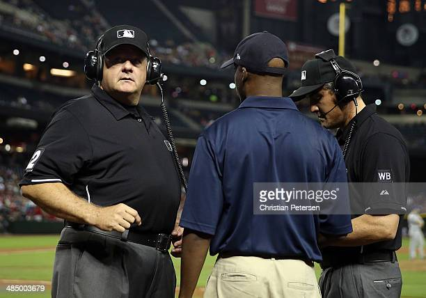 Second Base umpire Jerry Layne and First Base umpire Mike Dimuro stand with an instant replay official as they review a disputed call at first base...