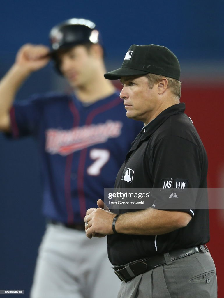 Second base umpire Marvin Hudson #51 during the Toronto Blue Jays MLB game as Joe Mauer #7 of the Minnesota Twins stands on second base on October 3, 2012 at Rogers Centre in Toronto, Ontario, Canada.