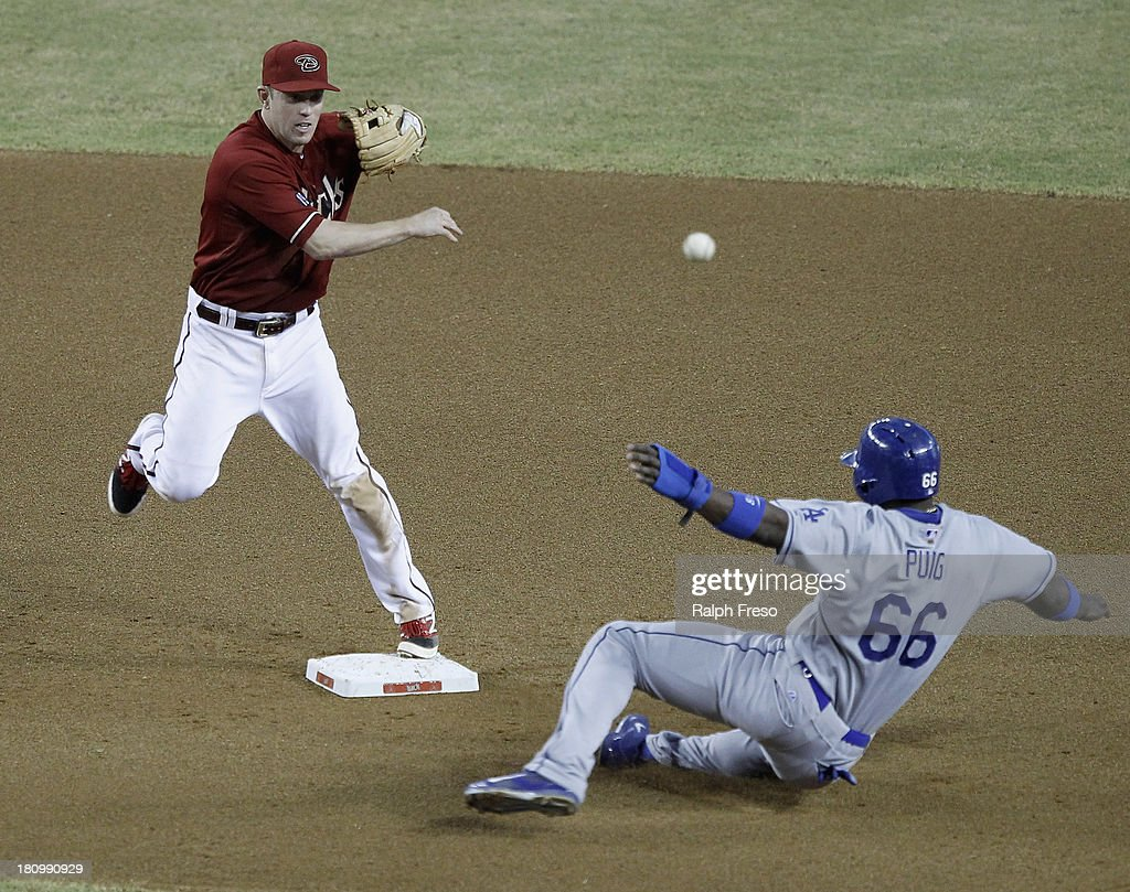 Second baseman <a gi-track='captionPersonalityLinkClicked' href=/galleries/search?phrase=Aaron+Hill+-+Baseball+Player&family=editorial&specificpeople=239242 ng-click='$event.stopPropagation()'>Aaron Hill</a> #2 of the Arizona Diamondbacks forces out <a gi-track='captionPersonalityLinkClicked' href=/galleries/search?phrase=Yasiel+Puig&family=editorial&specificpeople=10484087 ng-click='$event.stopPropagation()'>Yasiel Puig</a> #66 of the Los Angeles Dodgers as he throws to first to complete a double play during the seventh inning of a MLB game at Chase Field on September 18, 2013 in Phoenix, Arizona.