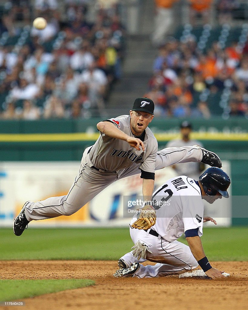 Second baseman Aaron Hill of the Toronto Blue Jays throws to first base while avoiding the slide from catcher Alex Avila of the the Detroit Tigers...