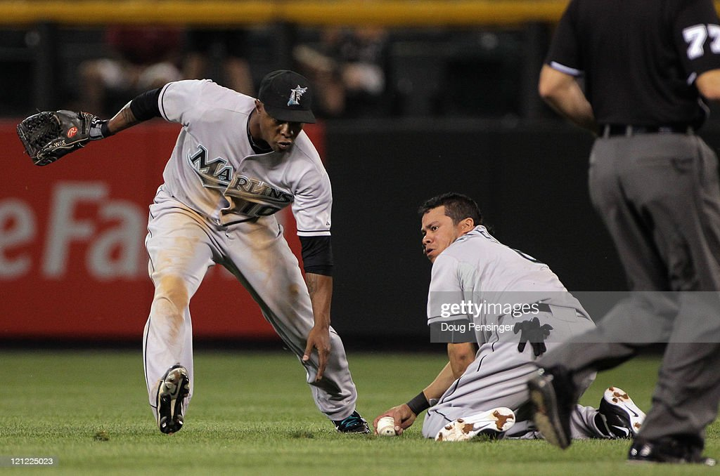 Second baseman <a gi-track='captionPersonalityLinkClicked' href=/galleries/search?phrase=Alfredo+Amezaga&family=editorial&specificpeople=239472 ng-click='$event.stopPropagation()'>Alfredo Amezaga</a> #6 of the Florida Marlins fields a soft fly ball as Dexter Fowler #24 of the Colorado Rockies doubles in the ninth inning while Dewayne Wise #10 of the Florida Marlins looks on at Coors Field on August 15, 2011 in Denver, Colorado. The Rockies defeated the Marlins 7-4.