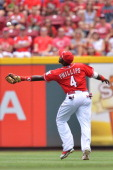 Second baseman Brandon Phillips of the Cincinnati Reds makes a catch running back into center field off a hit from Khris Davis of the Milwaukee...
