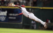 Second baseman Brandon Phillips of the Cincinnati Reds makes a diving catch on a line drive against the Houston Astros at Minute Maid Park on May 9...