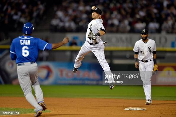 Second baseman Carlos Sanchez of the Chicago White Sox forces out Lorenzo Cain of the Kansas City Royals and leaps into air as he throws to first...