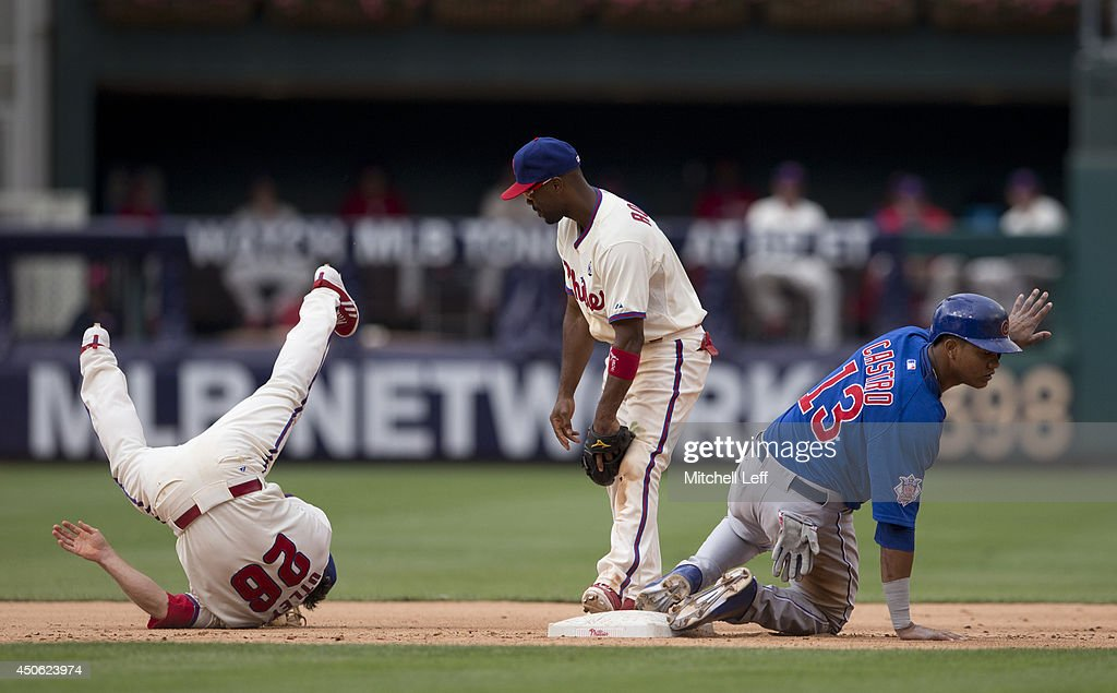 Second baseman Chase Utley #26 and shortstop Jimmy Rollins #11 of the Philadelphia Phillies collide as they attempt to turn a double play in the top of the sixth inning as shortstop Starlin Castro #13 of the Chicago Cubs slides into second on June 14, 2014 at Citizens Bank Park in Philadelphia, Pennsylvania.