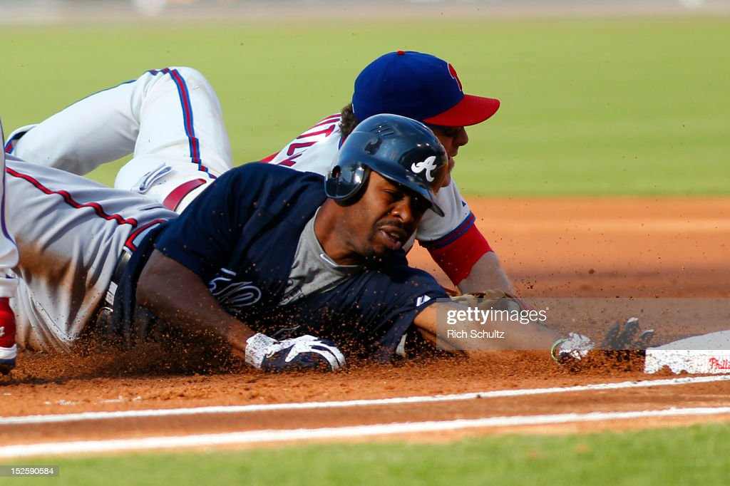 Second baseman <a gi-track='captionPersonalityLinkClicked' href=/galleries/search?phrase=Chase+Utley&family=editorial&specificpeople=161391 ng-click='$event.stopPropagation()'>Chase Utley</a> #26 of the Philadelphia Phillies dives and tags out <a gi-track='captionPersonalityLinkClicked' href=/galleries/search?phrase=Michael+Bourn&family=editorial&specificpeople=835742 ng-click='$event.stopPropagation()'>Michael Bourn</a> #24 of the Atlanta Braves who was caught in a rundown between first and second base after being picked off during the first inning in a MLB baseball game on September 22, 2012 at Citizens Bank Park in Philadelphia, Pennsylvania.