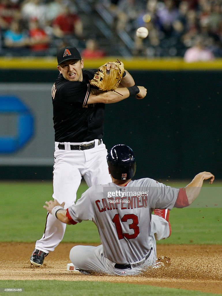 Second baseman Cliff Pennington of the Arizona Diamondbacks throws over Matt Carpenter of the St Louis Cardinals to complete a double play during the...