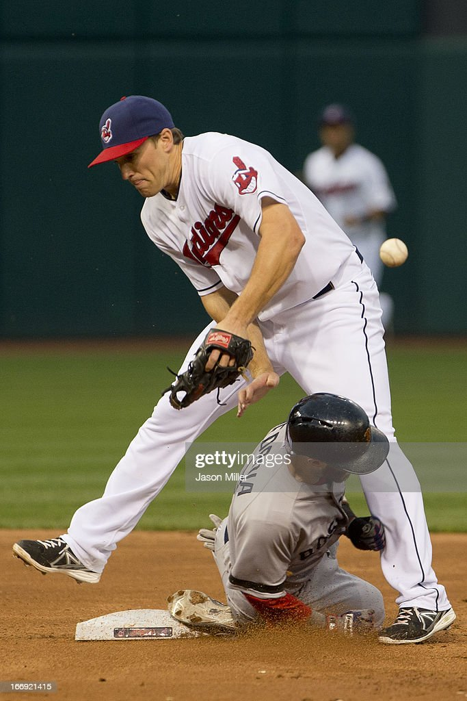 Second baseman Cord Phelps #46 of the Cleveland Indians drops the throw as Dustin Pedroia #15 of the Boston Red Sox steals second during the third inning at Progressive Field on April 18, 2013 in Cleveland, Ohio.