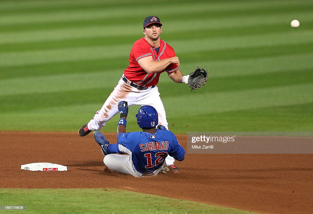 Second baseman Dan Uggla #26 of the Atlanta Braves throws to first base for a double play while left fielder Alfonso Soriano #12 of the Chicago Cubs slides in to attempt to distract the throw during the game at Turner Field on April 5, 2013 in Atlanta, Georgia.