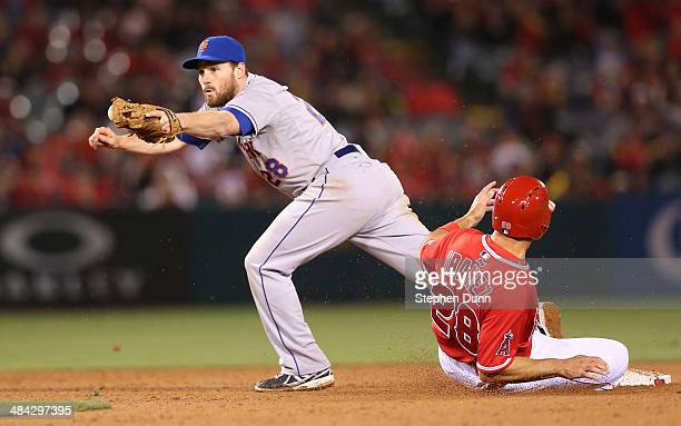 Second baseman Daniel Murphy of the New York Mets hangs on to the ball to froce out Raul Inbanez of the Los Angeles Angels of Anaheim for the second...